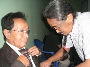 Singer Amrit Gurung fixes a tie on his guru, Ambar Dai, before the Nepalganj concert. PHOTO: KUNDA DIXIT