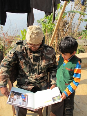 Gyanendra's father and son Aswin look at the story about him in the book, People After War.
