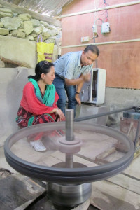 Barsha Shrestha of Clean Energy Bank inspecting an improved water mill