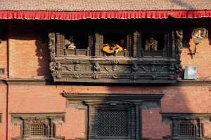 Tourists take photographs and videos of the flash mob from the Patan Museum.