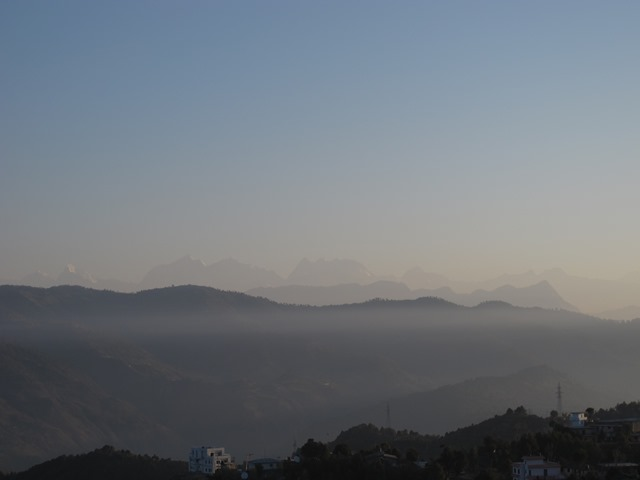 Sunrise in Dadeldhura reveals layers of hills shaded by morning mist and hazy outline of the Api-Saipal range in Humla to the north.