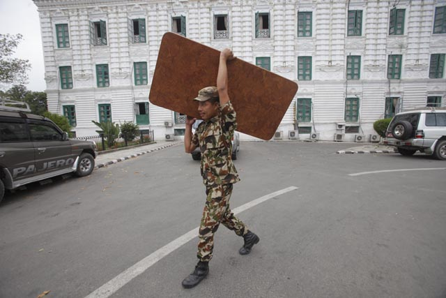 An army personnel helps move the furniture from the Prime Minister's Office in Singha Darbar.