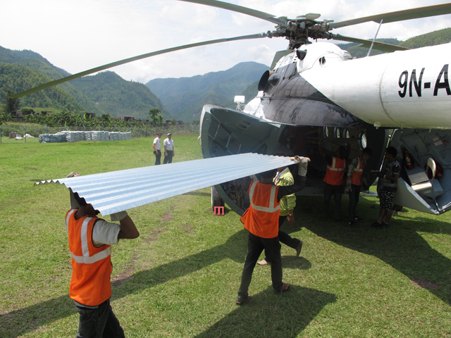 Corrugated sheets loaded onto the belly of one of five MI8 helicopters that fly relief supplies to remote villages .