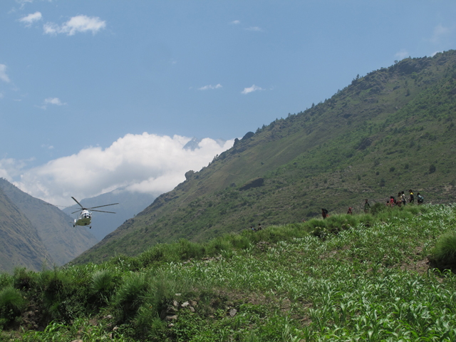 A helicopter loaded with supplies approaches for a landing at Philim in northern Gorkha which has been cut off because landslides after the quake wiped out even foot trails.