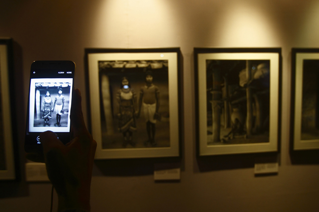 A visitor takes a photo of photographs on display during Photo Kathmandu.