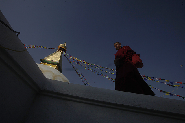 A monk circumambulates the Boudhanath Stupa.