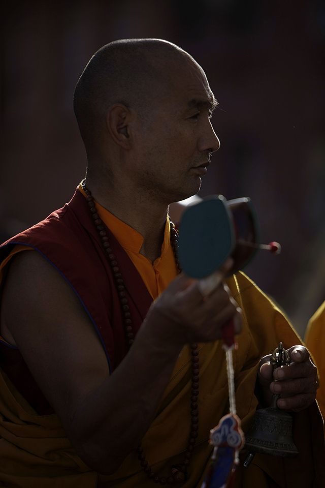 A Buddhist monk plays a pellet drum during the consecration ceremony of Boudhanath Stupa.