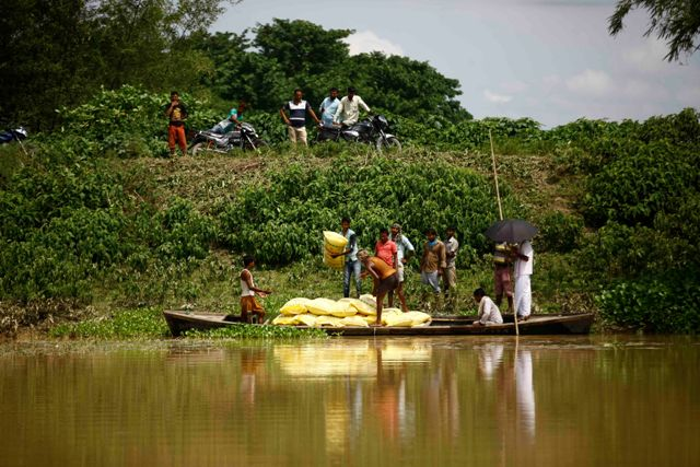 Villagers load food materials onto a boat.
