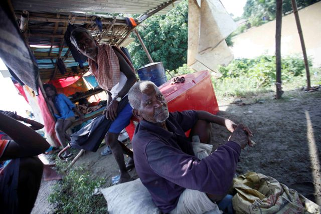 Villagers wait in makeshift-shelters