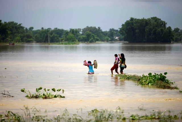 Villagers wade through a flooded road in Saptari