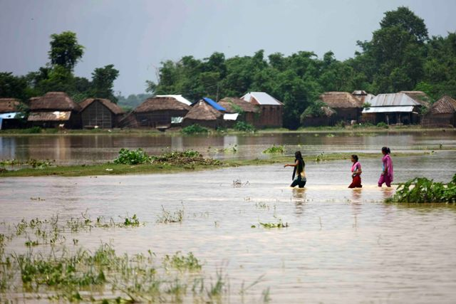 Villagers make their way to their homes through a flooded street in Saptari.