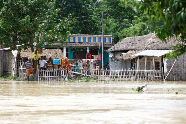 Villagers in Saptari wait outside their homes.