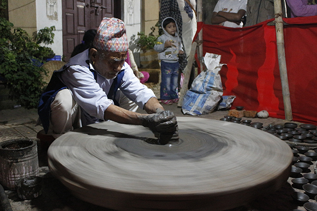 Mohan Singh Prajapati, 80, a member of the Jyapu community demonstrates his traditional occupation of pottery making during this week's festival in Patan on Wednesday. He has been making pottery for most of his life.