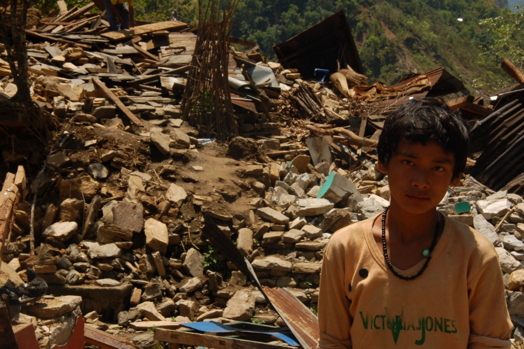 A boy stands infront of the rubble of his house where six people were buried.