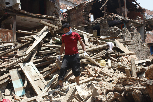 Upendra Maharjan standing on debris of his house Pic: Stéphane Huët