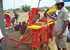 A manual compactor being used to make Compressed Stabilised Earth Blocks for a school in Bardiya.
