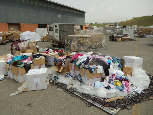 Relief materials scattered in the open outside TIA's cargo. Pic: Stéphane Huët