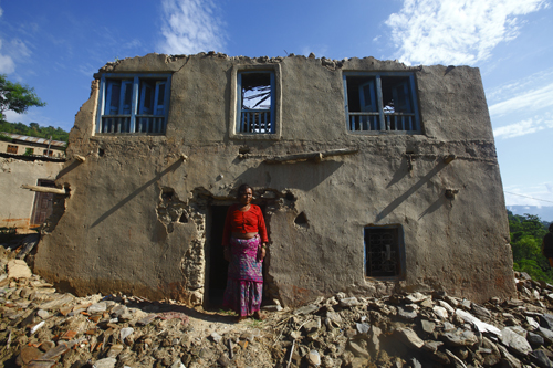 56-year old Dev Kumar Mijar stands in front of the remains of her two-storey house.