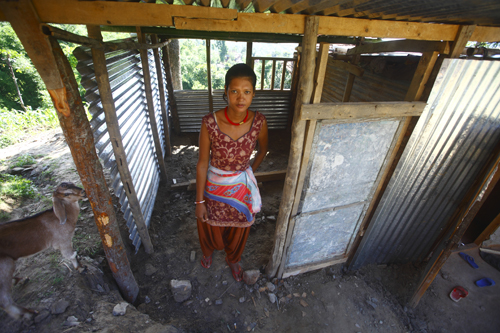Kamala Mijar stands in front of her unfinished temporary shelter.