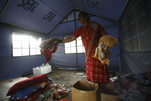 Saraswati Thapa packs her belongings into cardboard boxes.