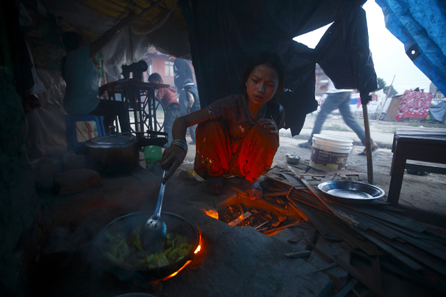 13-year-old Monika Tamang cooks food inside a temporary shelter in Chuchepati  where her family moved after their house was destroyed in the April 25 earthquake. She has been using firewood to cook food due to the gas shortage caused by the ongoing Indian blockade.
